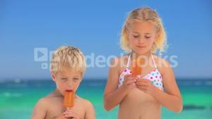 Blond children eating water ices on the beach