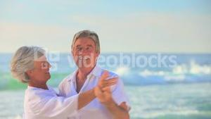 Mature couple dancing at the edge of the sea
