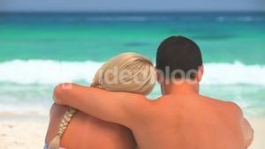 Sweet couple sitting hugging on a beach