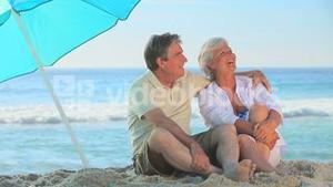 Elderly couple laughing under a beach umbrella