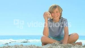 Young smiling boy listening to a shell