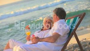 Elderly couple drinking cocktails on the beach