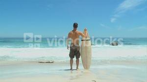 Man looking at the sea before going surfing