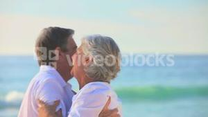 Elderly couple dancing on a beach