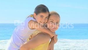 Woman giving daughter a piggyback on the beach