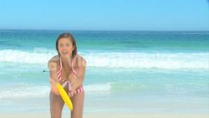 Woman in stripped swim suit playing frisbee