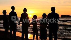 Family holding hands at sunset