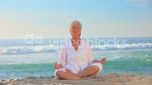 Mature woman in white doing yoga