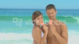 Sweet couple eating water ices with their backs to the sea