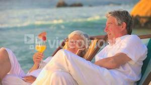 Mature couple drinking cocktails on the beach