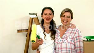 Mother and daughter smiling and showing their brushes at the camera