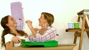 Mother trying to paint her daughter nose with brush