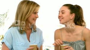 Mother and daughter talking and holding glasses