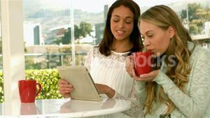 Pretty girls using tablet and drinking