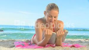 Georgeous blonde woman reading on a beach