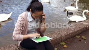 Businesswoman using her phone and tablet outside