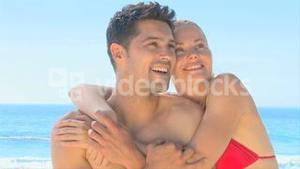 Happy couple hugging on a beach