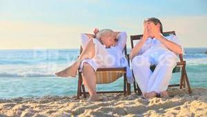Elderly couple sitting in deckchairs on a beach