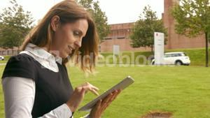 Businesswoman using tablet outside
