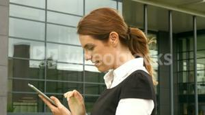 Businesswoman using phone outside
