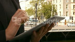 Businesswoman using her tablet outside