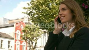 Businesswoman using her phone outside
