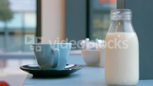 Milk jug and cup on cafe table