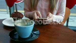 Pretty blonde having a coffee texting on phone