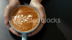 Hands around a cup of cappuccino
