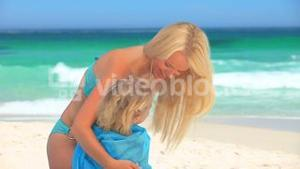 Mother drying her daughter with beach towel