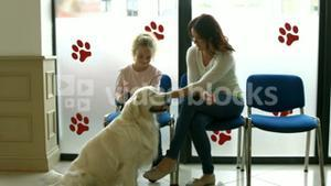 Mother and daughter with dog in vet waiting room