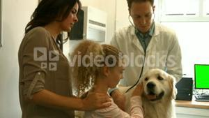 Mother and daughter with dog in the vets