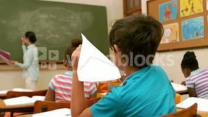 Child with paper plane in the hand during the lesson