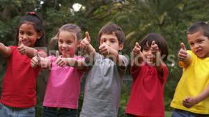 Children raising their thumbs and smiling