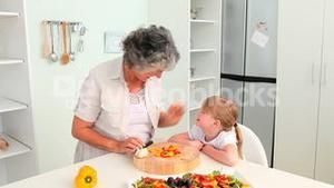 Grandmother cooking with her granddaughter