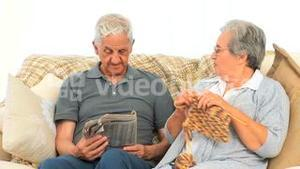 Woman knitting while her husband is reading the newspaper