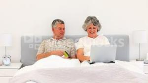 Couple buying something on the net in the bed