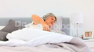 Retired woman waking up with a pain back