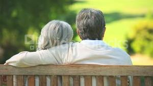 Elderly couple talking while sitting on a bench