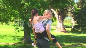 Young mother giving her daughter a piggyback