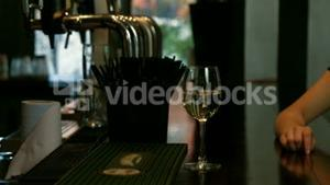 Bartender serving white wine to woman