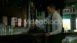 Bartender using cash register and tidying up the counter