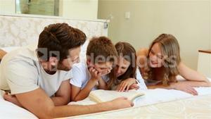 Happy family on the bed reading book