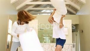 Siblings having pillow fight together