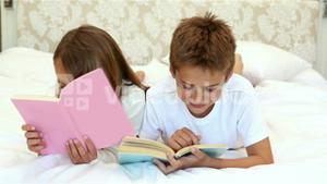 Children reading a book on the bed