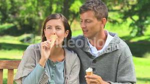 Young couple eating icecream outdoors