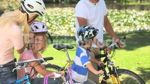 Two children cycling with their parents
