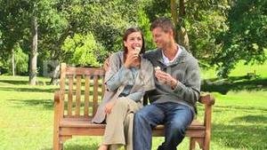 Young couple eating icecream on a park bench
