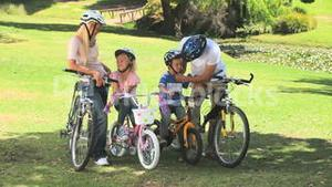 Young couple with their two children ready to go cycling