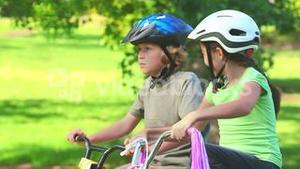 Young girl cycling with her brother